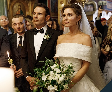 A scene from Keven Undergaro and wife, Maria Menounos's second wedding in Greece. The two standing side by side with a bouquet in her hand.