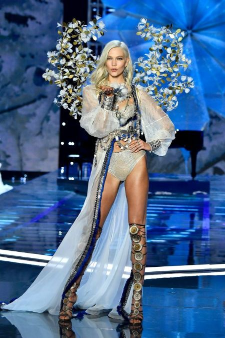 Angel Karlie kloss stands on the runway of Victoria's secret on white lingerie covered with a white robe with blue boarder and wings decorated with white flowers. Kloss is blowing a kiss on the stage