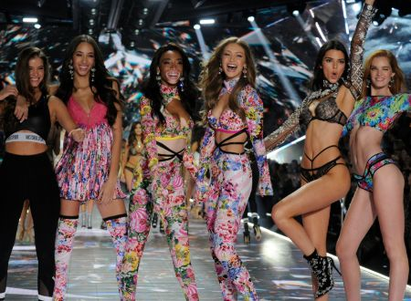 six models stand on the victoria's secret 2018 fashion runway strutting pose for the cameras. the model include Winnie Harlow, Gigi Hadid, Kendal Jenner and 3 other angels.
