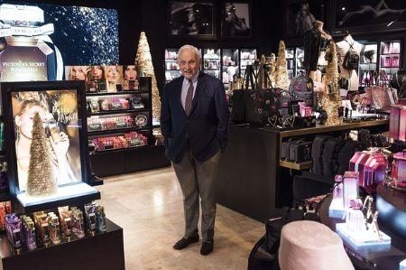 leslie wexner, the owner of Victoria Secrets stands in the middle of the VS store in a blue blazer and brown pants
