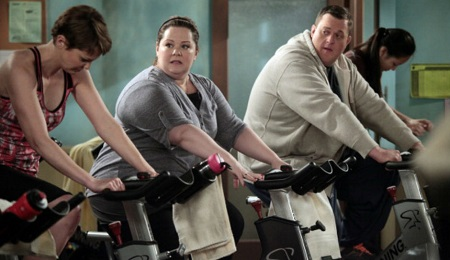 A scene from 'Mike & Molly' where the two characters are on treadmills.