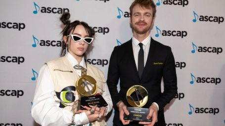 Billie eilish and her brother finneas on the ascap music awards holding 2 different awards, billie wearing a white coat with layered chains and gucci bag while finneas is in a tuxedo