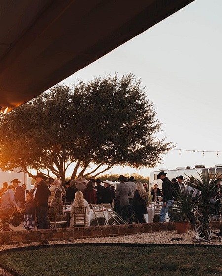 The moment of wedding reception captured from afar, people sitting and standing while surrounding the ranch tree.