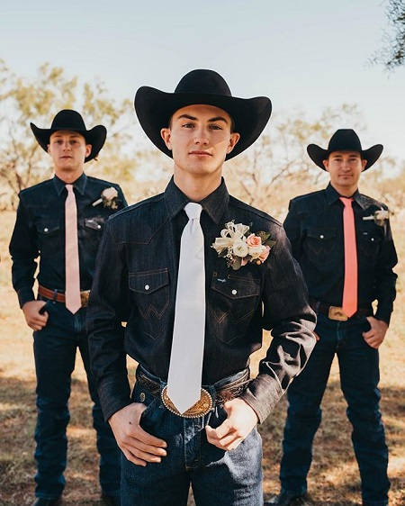 An iconic cowboys pose with Jess Lockwood and two of his groomsmen - both hands in one slot of the belt.
