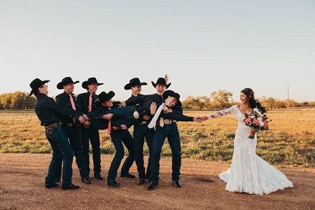 The groomsmen carrying the groom, Lockwood, as he extends his hand out to reach the bride, Kinsel, holding a bouquet.