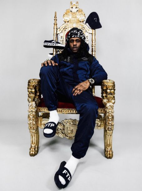 The rapper sitting on a golden throne looking chair in blue jacket and sweatpants with flipflops with 'FTP' written on it. alongside shoes and a hat hanging from the chair.