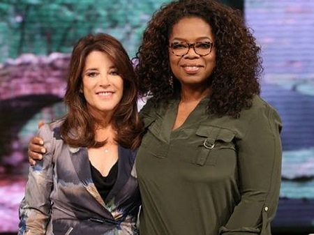 Oprah Winfrey holding Williamson by the shoulder.