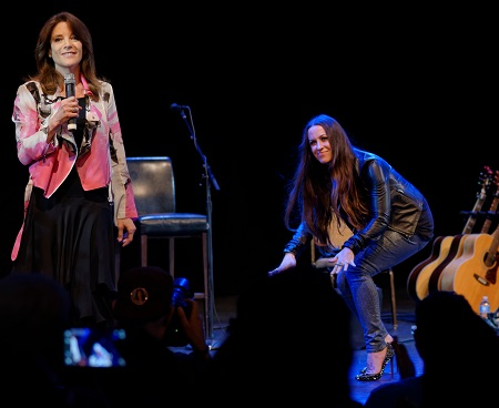Williamson holding a mic and Morissette crouching on stage.