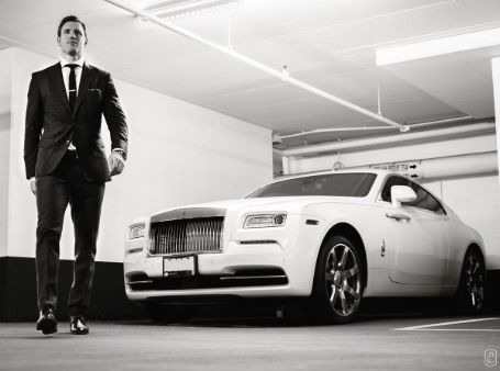 brooks in a black suit beside a white rolls royce