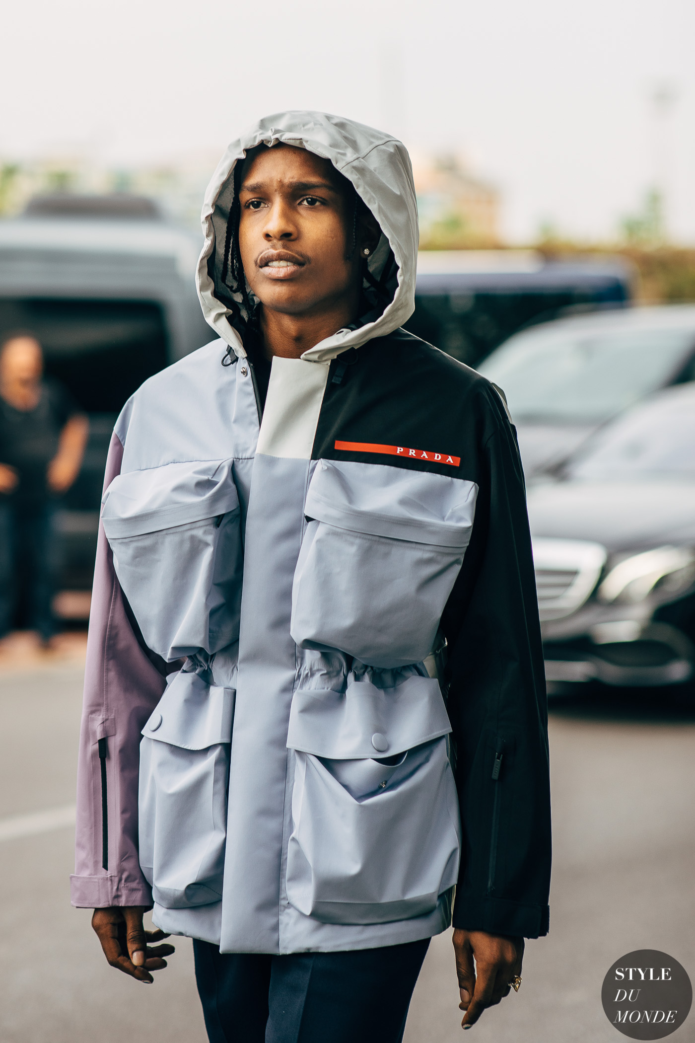 asap rocky wearing a grey and black jacket strutting on the street