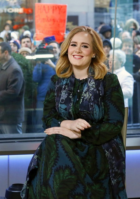 Adele sitting on a chair smiling at the camera. Glass window on the background with paparazzis.