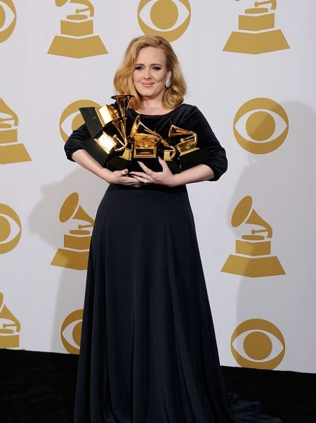 Adele in black holding six Grammys in her arms smiling at the camera.