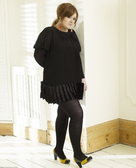 Adele in all black posing while leaning on a wall.