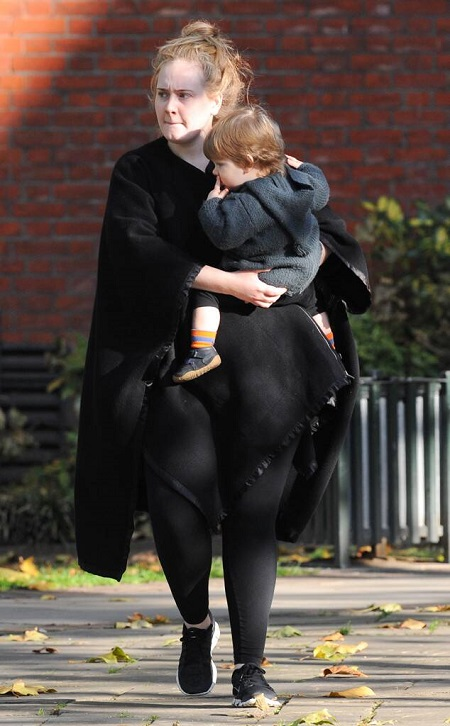 Adele in black carrying her son Angelo in 2015.