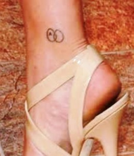 Two interlocked circles with letter 'A' on Scarlett Johansson's right ankle.