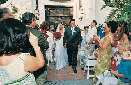 Lynette Romero and husband David Angulo walking the outdoor aisle on their wedding day. Lynette holding the bouquet and smiling with husband.