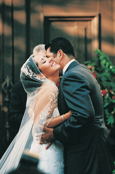 Lynette Romero with husband David Angulo on their wedding day, cozying and laughing it up in their wedding dresses.
