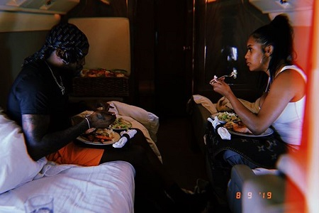 Meek Mill and Milan Harris eating breakfast while sitting on beds in a jet.