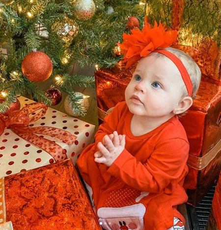 Baby Mila under a christmas tree dressed up in a red bodysuit.