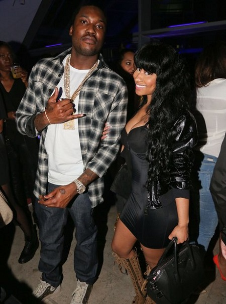 Nicki Minaj holding on to Meek Mill's hand with his other hand a signature of hip-hop.
