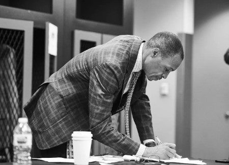 Gus writing on his desk.
