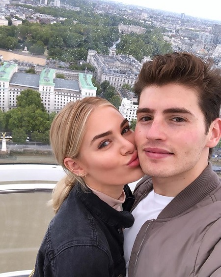 Michelle Randolph kissing Gregg Sulkin in the cheek as he takes the selfie. She too looking at the camera.