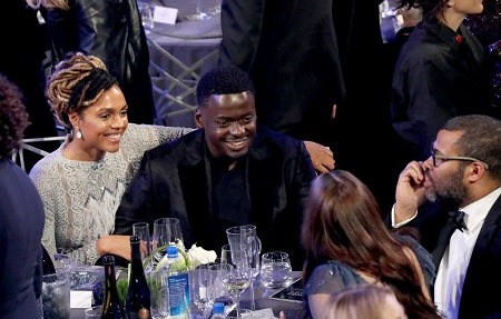 Amanda Crichlow with his arm around Daniel Kaluuya in a dinner table at the Golden Globe Awards.