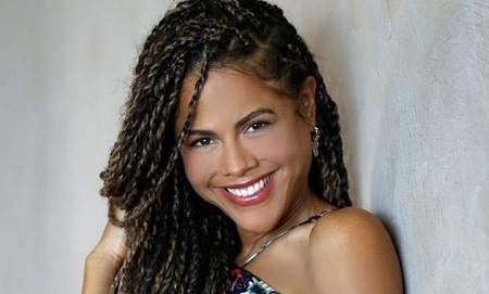 Lenora Crichlow headshot, smiling with braided hair pieces all over.