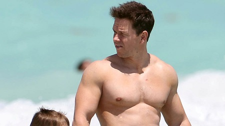 Wahlberg in the beach, shirtless and looking back as he walks with his daughter (not show).