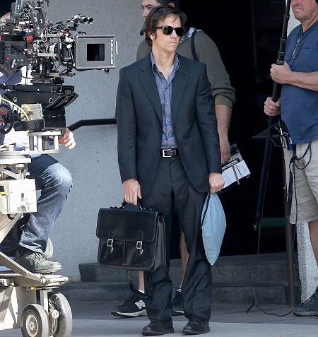 Wahlberg on the set of 'The Gambler' looking really thin and standing with a black briefcase.