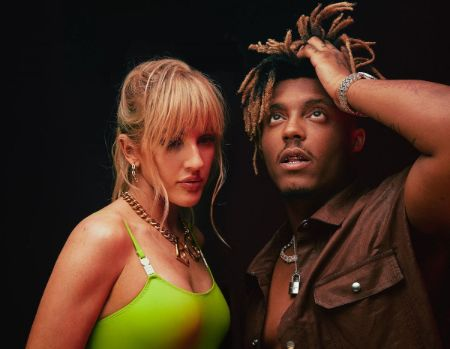 Juice Wrld and British Singer Ellie Goulding standing toegther. Ellie is in a neon top looking down. Juice is in a brown shirt with his hands caressing his hair looking up.