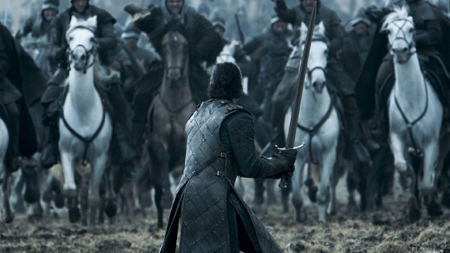 Jon Snow stands alone in a field against the Bolton army, with his sword drawn and ready to fight.