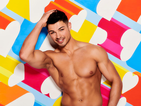 Anton Danyluk, bare chested, poses for the camera with his right hand slowly combing his hair.
