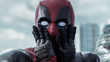 Deadpool is amazed by something he sees off screen and puts both his palms on his cheeks.
