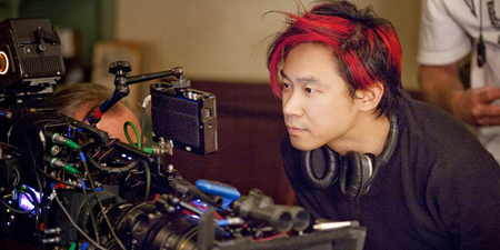 Jame Wan look at the camera with a headphone around his neck while filming.