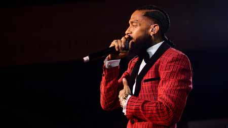 Nipsey Hussle holds a mic to his mouth and other hand to his chest.