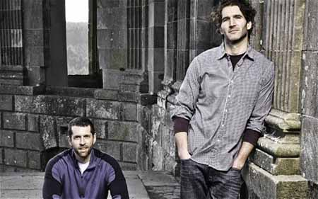 D.B. Weiss sits and David Benioff stands to take a photo.