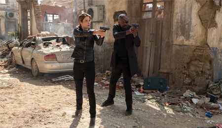 Maria Hill and Nick Fury stand in a ruined city in Mexico with their guns out.