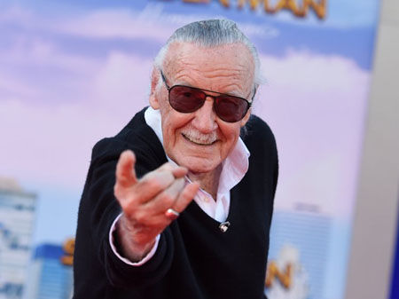Stan Lee poses like Spider-Man during the premiere of Spider-Man: Homecoming.