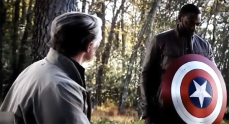 Sam holds Captain America's shield as Steve sits on a bench.