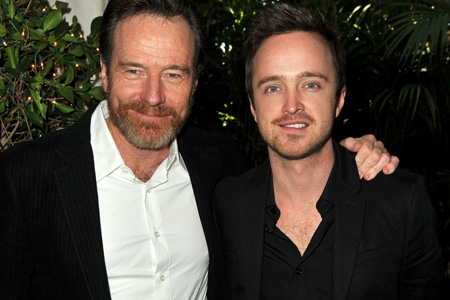 Bryan Cranston and Aaron Paul stand together to take a photo.