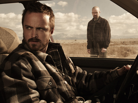 Aaron Paul is in the driving seat as Bryan Cranston looks through the window.