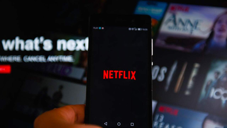 Mobile phone shows the Netflix logo as the background image also shows the Netflix front page.