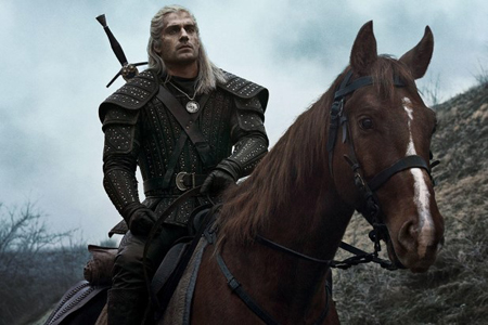 Henry Cavill rides a horse in the show The Witcher.