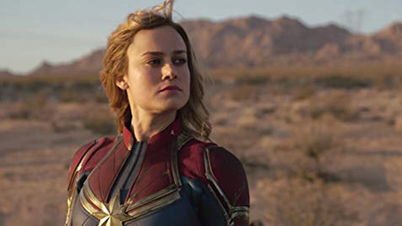 Captain Marvel on earth, looks off screen.