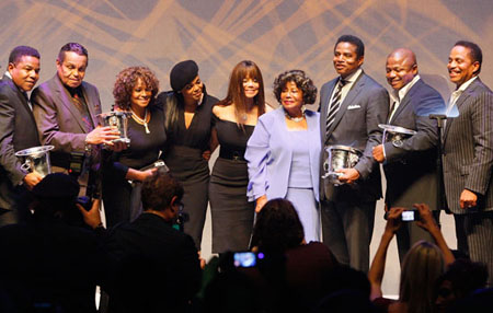 The Jackson family stand together on stage to accept the award.