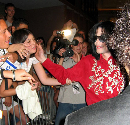 Michael Jackson touches the cheek of a fan.