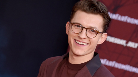 Tom Holland wearing glasses smiles to take a photo.