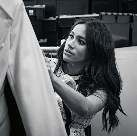 Meghan Markle looking at clothes inside a dressing room.