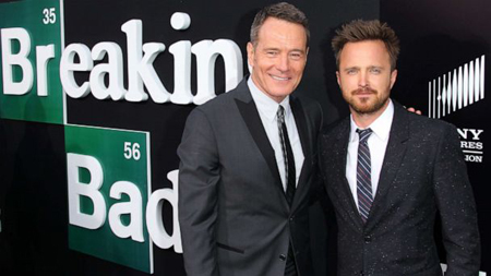 Bryan Cranston and Aaron Paul hug each in front of a Breaking Bad poster.